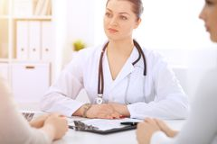 Brunette female doctor talking to patient at hospital office. Physician says about medical exams results for choosing. Optimal treatment. Healthcare and stock photo