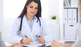 Brunette female doctor talking to patient in the hospital office. Physician says about medical exams results for Stock Image