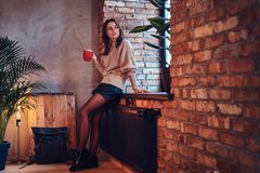 A woman drinks hot coffee in a room with loft interior. A brunette female dressed in a brown long neck jacket drinks hot coffee in a room with loft interior Stock Photos