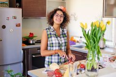 Brunette female in eyeglasses making salad from vegetables in the home kitchen. Attractive brunette female in eyeglasses making salad from vegetables in the Royalty Free Stock Images