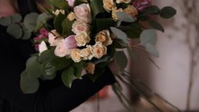 Brunette female floral artist holding beautiful bouquet of roses, tulips in pastel coloures at workshop. Gathering. Bouquet with flowers and plants. Floristry stock footage