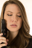 Brunette female holding a black pistol looking down Royalty Free Stock Image