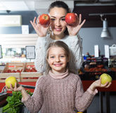 Brunette female with a little girl considering apples at store Stock Photo