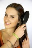 Brunette female model brushing long hair Stock Images