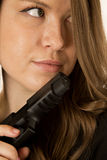 Brunette female model glancing sideways holding a black pistol Royalty Free Stock Image