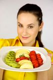 Brunette female model showing fresh fruit. On a plate with strawberries kiwi apple Stock Photography