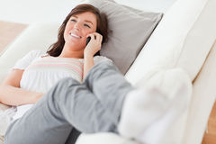 Brunette female on the phone lying on a sofa Stock Photo