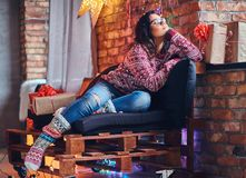 Brunette female in a room with Christmas decoration. Full body image of brunette female in eyeglasses dressed in a jeans and a red sweater posing on a wooden Royalty Free Stock Photo