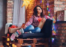 Brunette female in a room with Christmas decoration. Full body image of brunette female in eyeglasses dressed in a jeans and a red sweater posing on a wooden Royalty Free Stock Photography
