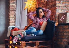 Brunette female in a room with Christmas decoration. Full body image of brunette female in eyeglasses dressed in a jeans and a red sweater posing on a wooden Stock Image