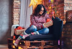 Brunette female in a room with Christmas decoration. Full body image of brunette female in eyeglasses dressed in a jeans and a red sweater posing on a wooden Stock Photo