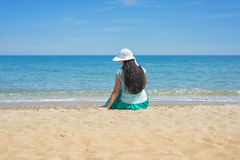 Brunette female sitting alone on the beach Stock Photo
