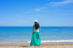 Brunette female standing alone on the beach Stock Images