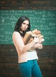 Brunette female student in classroom. Sexy young college girl walking with two heaps of books Royalty Free Stock Photo