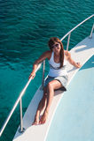 Woman tanning on shipboard of yacht. Brunette female tanning on shipboard of yacht in sunglasses Royalty Free Stock Photo