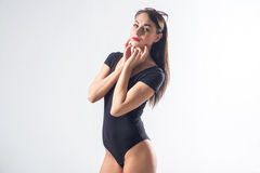 Brunette fit female standing in studio, touching her chin with fingers, wearing black swimwear, keeping sunglasses on Stock Image