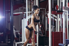 Brunette fitness girl in black sport wear with perfect body in gym stock images