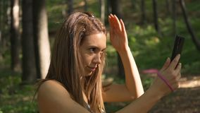 Brunette fitness girl fixing her hair for selfie photo. Beautiful fitness girl using mobile phone outdoors, sitting on a bench stock video footage