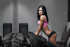 Brunette fitness woman in black sport in gym Royalty Free Stock Photography