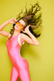 Brunette with flipping hair in pink jumpsuit and. Portrait of sexy young curly brunette wearing pink lycra jumpsuit. Amazing female wearing big yellow safety Royalty Free Stock Photos