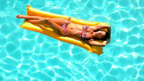 Brunette floating across the pool on lilo on sunny day stock video footage