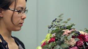 Brunette florist makes bouquet flower composition inside stock video