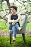 Brunette-Frau auf einem Stuhl draußen Lizenzfreie Stockfotos