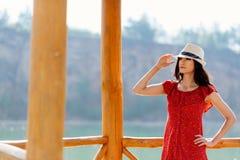 Brunette Frau der Schönheit im roten Kleid und im weißen Sonnenhut über dem See lizenzfreie stockfotografie