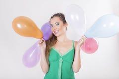Brunette-Frau, die Ballone auf ihrer Geburtstagsfeier hält Lizenzfreie Stockfotos