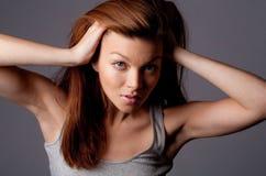 Brunette-Frau, die mit dem Haar spielt Lizenzfreie Stockfotografie