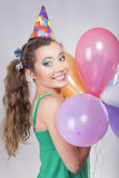 Brunette-Frau in einer Geburtstags-Kappe, die Ballone und Lächeln hält Lizenzfreie Stockfotos