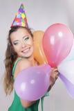 Brunette-Frau in einer Geburtstags-Kappe, die Ballone und Lächeln hält Stockfoto