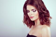 Brunette-Frau mit dem langen glänzenden gewellten Haar Stockfoto
