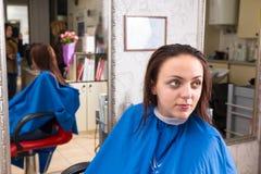 Brunette-Frau mit dem nassen Haar, das in Salon wartet Stockfoto