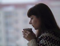Brunette Frau trinkt Kaffee und schaut heraus das Fenster durchdacht stockfoto
