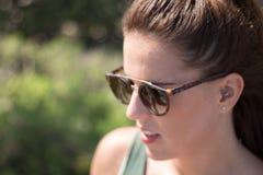 Brunette Frauenseiten-Porträtstellung äußer, schauend links, mit unfocused Hintergrund stockfotos