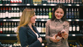 The brunette with friend choose the wine in the supermarket. Beautiful girls standing near the stand with bottles of wine. Two friends are talking and choosing stock video