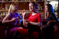 Brunette with friends in bar. Attractive brunette with two pretty friends in cocktail bar Royalty Free Stock Photography