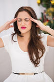 Brunette getting a headache on christmas day Stock Photography