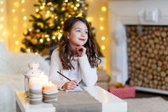 A brunette gilr in front of fur-tree writing a letter to santa claus. A girl dreaming. New year`s eve. Christmas stock photography