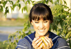 Brunette girl and apple. Beautiful brunette girl wants to eat apple Royalty Free Stock Photos