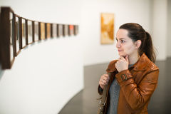 Brunette girl in art museum. Portrait of happy adult brunette girl in art museum stock photos