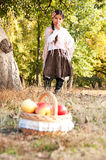 Brunette girl with basket of ripe apples Stock Photos