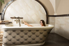 Brunette girl in a bathtub Stock Photo