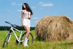 Brunette girl on bicycle in the field Stock Photos