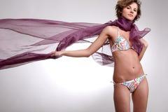 Brunette girl in bikini. Young beautiful brunette girl in bikini with violet scarf on white background Stock Image