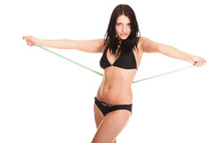 Brunette girl bikini measuring waistline tape Royalty Free Stock Photo