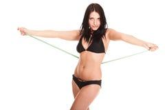 Brunette girl bikini measuring waistline tape royalty free stock photo