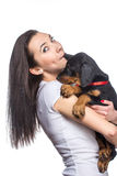 Brunette girl biting her doberman puppy by ear Royalty Free Stock Photo
