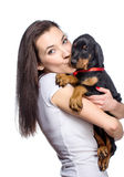 Brunette girl biting her doberman puppy by ear Royalty Free Stock Photos